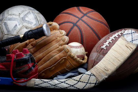 assorted sports equipment on a black background